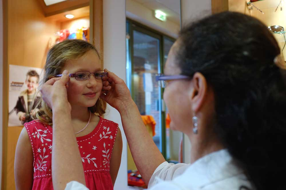 Optician with a child trying on glasses